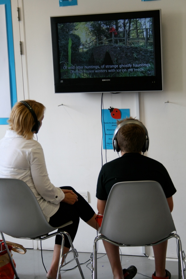 Older child and woman listening raptly to poetry on video. Part of the Poetry Immersion Kit available when I visit schools. Immerse your class in words and images and sensory input that will inspire the best writing! I also give workshops and readings, lizpoet @ gmail.com